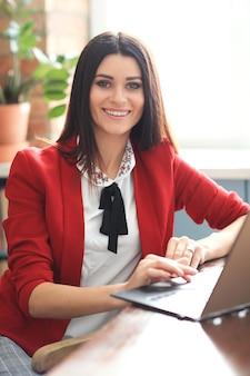 Moda joven mujer morena trabajando desde casa con ordenador portátil. concepto de teletrabajo