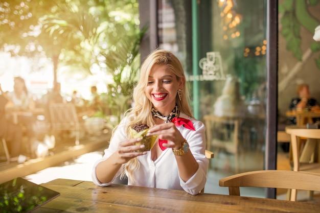 Moda joven mujer sentada en la cafetería comiendo muffin