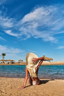 Moda joven mujer sentada en la orilla de la playa