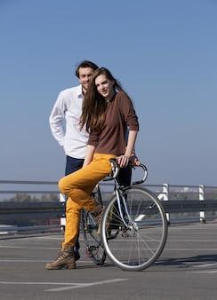 Moda joven pareja posando con bicicleta al aire libre