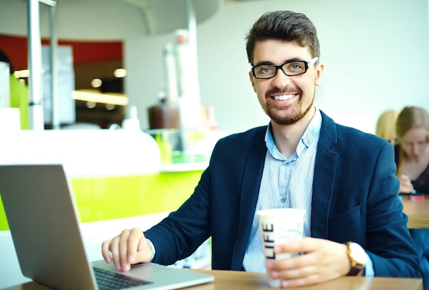 Moda joven sonriente hipster hombre tomando café en la cafetería de la ciudad durante la hora del almuerzo con cuaderno en traje