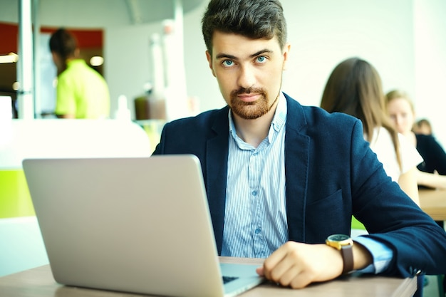 Moda joven sonriente hombre hipster en el café de la ciudad durante la hora del almuerzo con cuaderno en traje