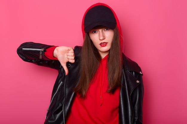 Moda joven usa lápiz labial rojo brillante, usa camisa elegante, chaqueta de cuero y gorra negra. tenager descarado muestra signo de dedo hacia abajo