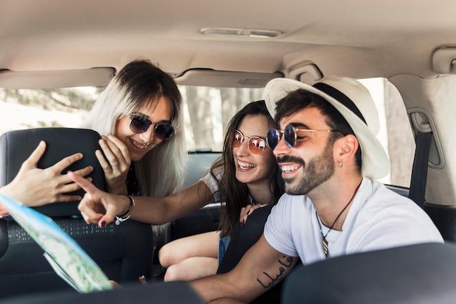 Moda jóvenes amigos sentados dentro del coche moderno mirando el mapa
