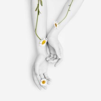 Moda mano arte manzanilla cosmética natural mujeres, blanco hermosas flores de manzanilla mano con maquillaje de contraste brillante, cuidado de las manos. foto de belleza creativa mujer sentada en la mesa