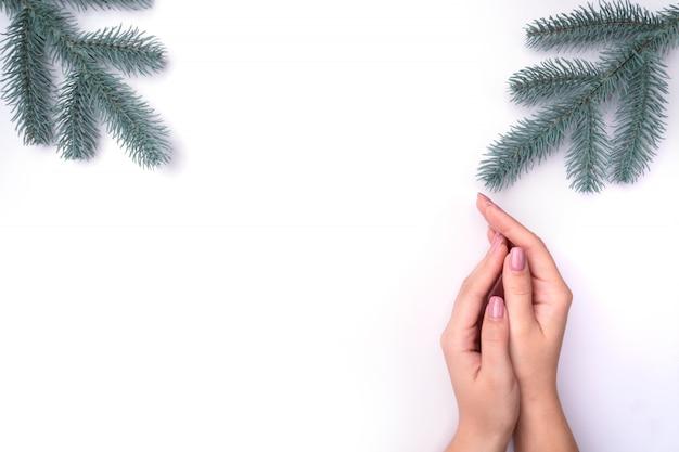Moda, manos de mujer con manicura, cuidado de uñas, ramitas de árboles de navidad