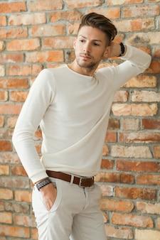 Moda masculina sobre piso de madera, joven posando