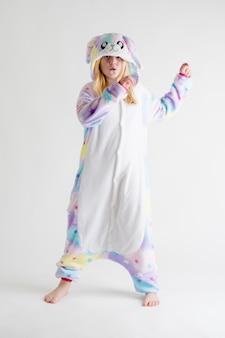 Moda moderna - hermosa chica rubia posando sobre un fondo blanco en pijama kigurumi, disfraz de conejito