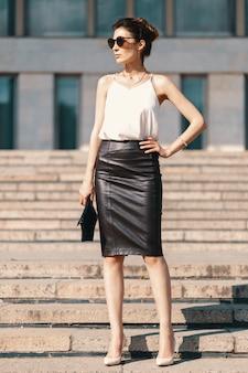 Moda morena empresaria en falda lápiz de cuero
