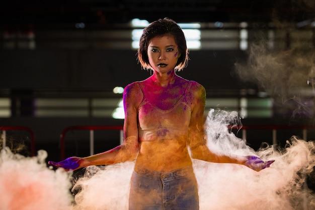 Moda mujer asiática con polvo de colores y humo multicolor en el aire