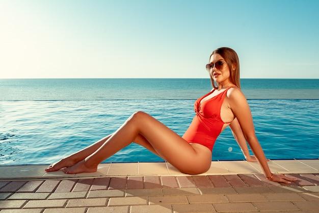 Moda mujer en bikini rojo sentada cerca de la piscina