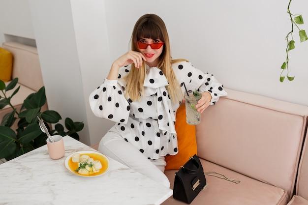 Moda mujer en elegante blusa y gafas rojas disfrutando el fin de semana en la cafetería