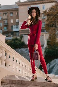 Moda mujer elegante hermosa en traje púrpura caminando en las calles de la ciudad, tendencia de moda primavera verano otoño temporada con sombrero, sosteniendo el bolso
