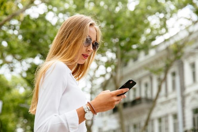 Moda mujer hermosa con largo cabello rubio usando un teléfono móvil, mientras camina al aire libre