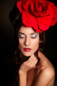 Moda mujer hermosa con maquillaje brillante y labios rojos con gran rosa roja en la cabeza