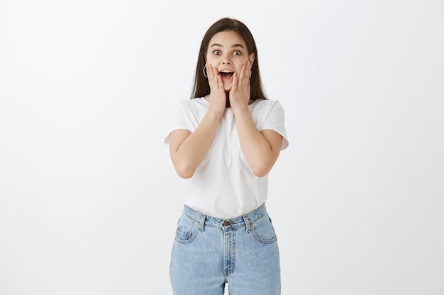 Moda mujer joven emocionada posando contra la pared blanca