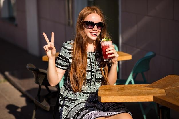 Moda mujer joven con pelos largos y una sonrisa increíble, sosteniendo una deliciosa limonada de cóctel de verano dulce