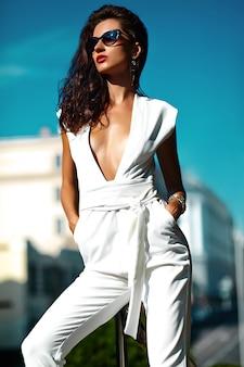Moda mujer mujer modelo en traje blanco con gafas de sol en la calle