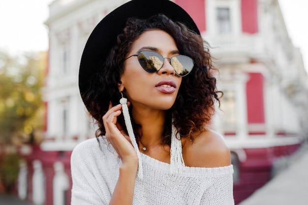Moda mujer negra con elegantes pelos afro posando al aire libre. fondo urbano lleva gafas de sol negras, sombrero y aretes blancos. accesorios de moda. sonrisa perfecta.