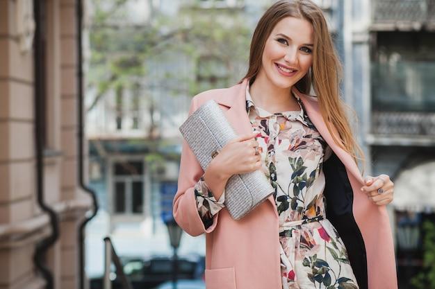 Moda mujer sonriente con estilo atractivo caminando calle de la ciudad en abrigo rosa tendencia de moda de primavera con bolso