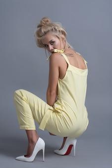 Moda mujeres jóvenes en vestido de moda, maquillaje. elegante peinado ondulado, traje amarillo. maquillaje posando cerca de un barril negro sobre un fondo gris