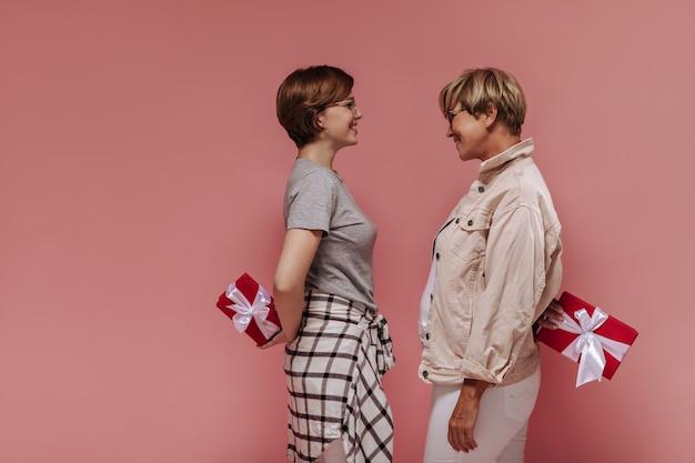 De moda para mujeres con peinado corto y fresco y gafas con ropa ligera mirándose, sonriendo y sosteniendo cajas de regalo rojas sobre fondo rosa.