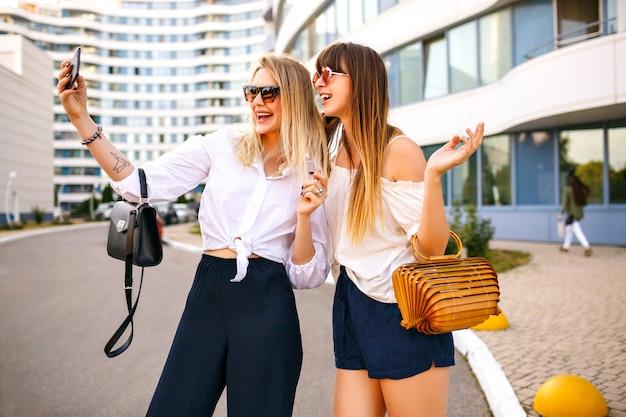 Moda pareja de hermosa mujer elegante de moda con trajes femeninos clásicos, bolsos y gafas de sol de verano a juego, haciendo que selfie termine disfrutando del tiempo juntos, estado de ánimo de viaje, verano.
