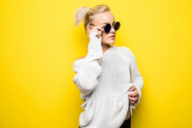 Moda seria chica rubia en suéter blanco moderno con gafas de sol azules brillantes está posando en amarillo