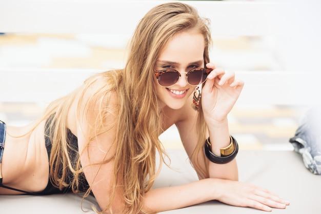 Moda de verano. chica junto a la piscina. mujer sexy en gafas de sol de moda y traje de baño de bikini de moda y disfrutando de vacaciones de lujo en el resort hotel.