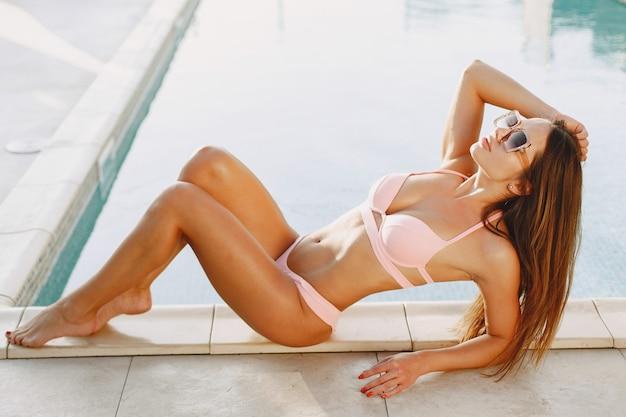 Moda de verano. mujer en traje de baño junto a la piscina. señora de vacaciones.