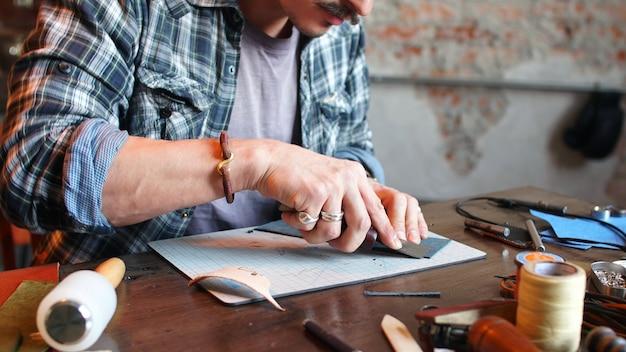 Modelando el diseño de una billetera, billetera a pedido. lugar de trabajo de un artesano de cuero en el taller.