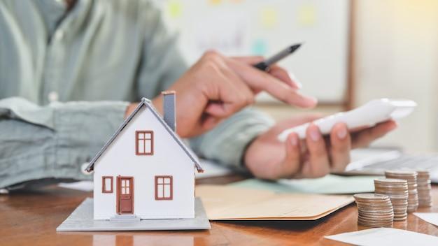 Modele casas y monedas con personas que usan la calculadora, concepto de costo de la casa.