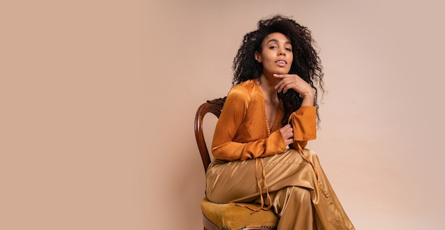Modelo africano seductor joven de moda con pelos rizados perfectos en elegante blusa naranja y pantalones de seda sentado en la pared beige de la silla vintage.