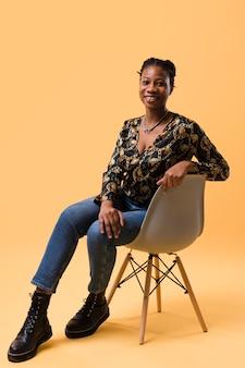 Modelo afroamericana sentada en silla