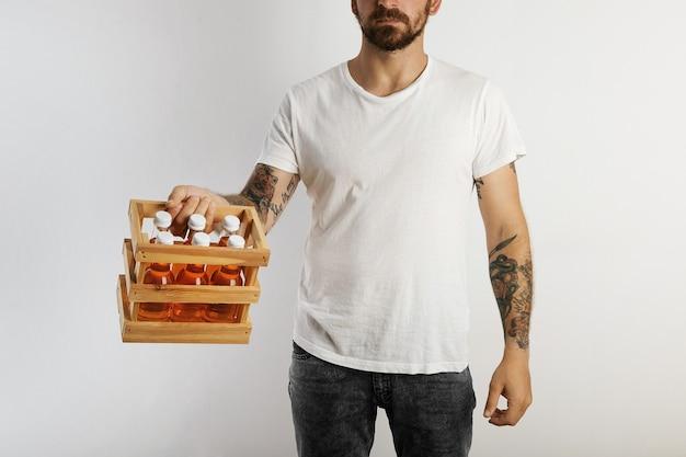 Un modelo de ajuste joven con tatuajes y barba sosteniendo un sixpack de bebidas naranjas sin etiqueta aislado en blanco