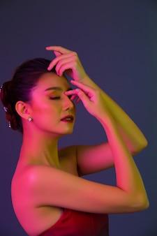 Modelo de alta moda mujer en coloridas luces brillantes posando
