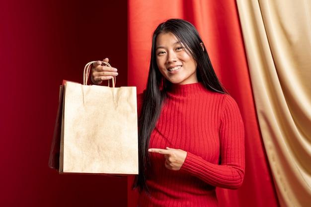 Modelo apuntando a la bolsa de papel para el año nuevo chino