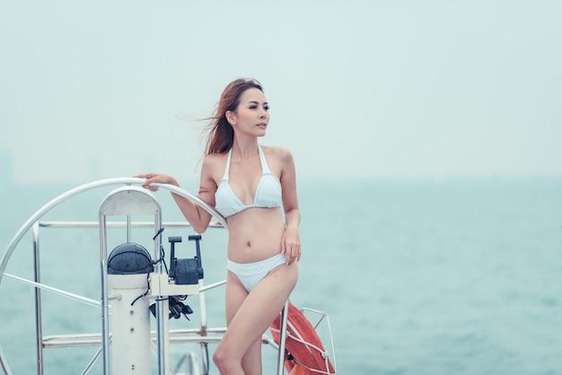 Modelo asiática en bikini blanco en un yate.