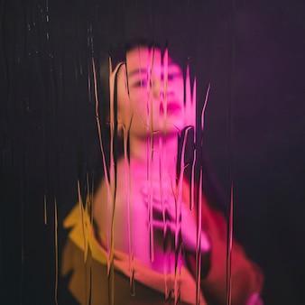 Modelo asiático posando con luz rosa sobre ella