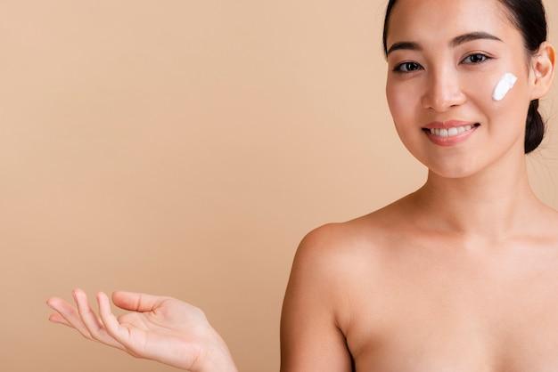 Modelo asiático de primer plano con crema para la cara y espacio de copia