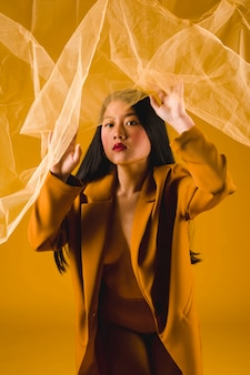 Modelo asiático de la vista delantera con el fondo amarillo