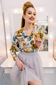 Modelo atractivo y elegante en falda de tul, con peinado de lujo, hermoso maquillaje sonriendo a la cámara en la peluquería con una copa de champán