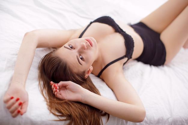 Modelo atractivo de la mujer joven que miente en cama