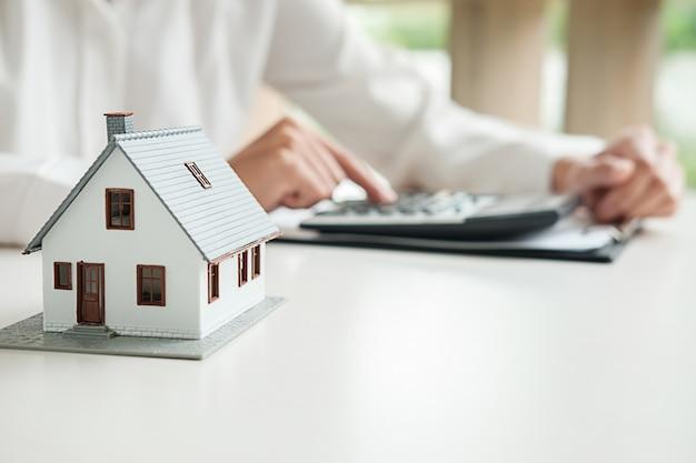 Modelo de automóvil y casa con agente y cliente que discuten el contrato para comprar, obtener un seguro o un préstamo de bienes raíces o antecedentes de la propiedad.