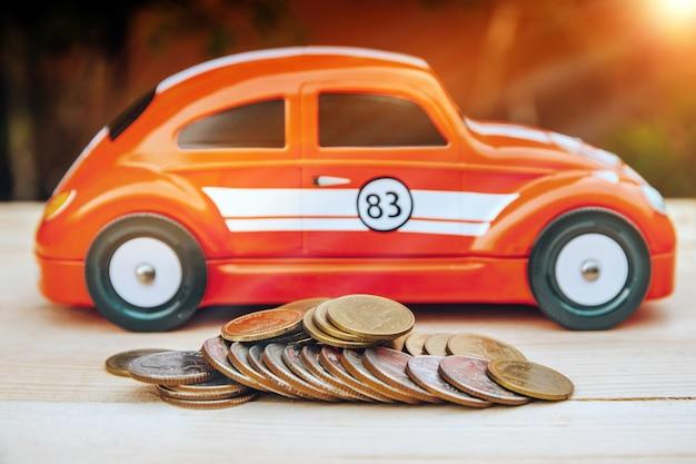 Modelo de automóvil en mesa de madera con moneda de baht tailandés que ahorra dinero o concepto de seguro
