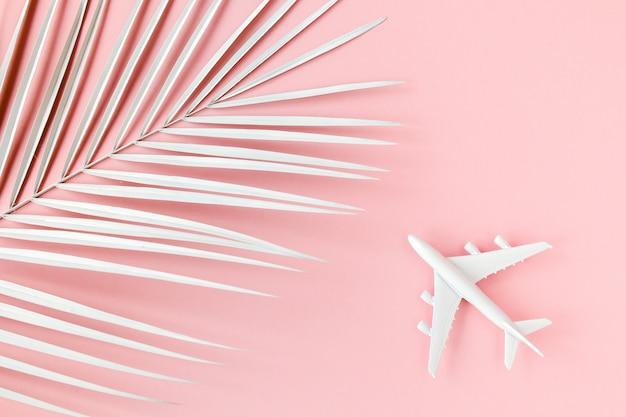 Modelo de avión blanco junto a una hoja de palma sobre fondo rosa
