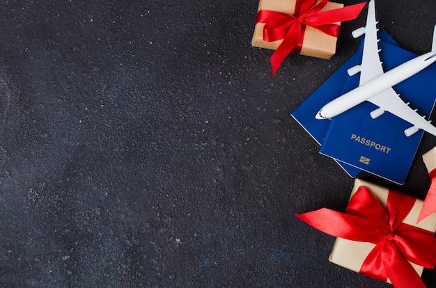 Modelo de avión, cajas de regalo y pasaportes sobre fondo oscuro. concepto de viaje.