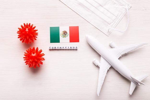 Modelo de avión y mascarilla y bandera de méxico. pandemia de coronavirus. prohibición de vuelos y cierre de fronteras para turistas y viajeros con coronavirus covid-19 de europa y asia.
