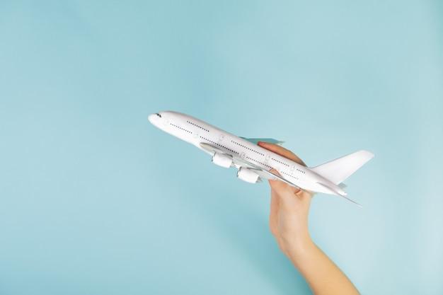Modelo de avión a reacción en mano humana sobre fondo azul. concepto de un avión despegando y volando hacia los cielos