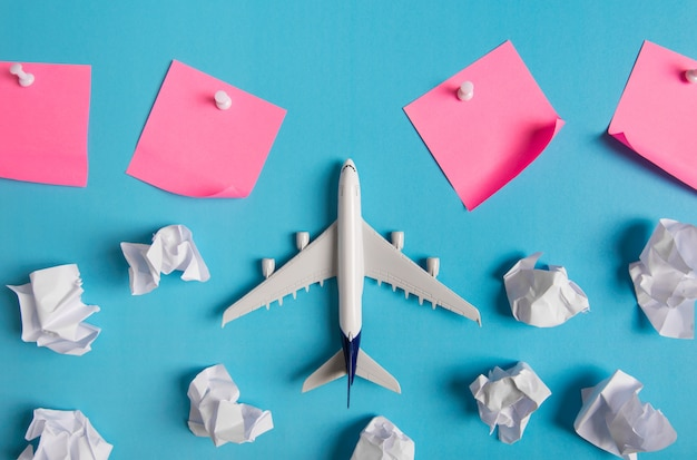 Modelo de avión volando entre nubes de papel y papel rosa